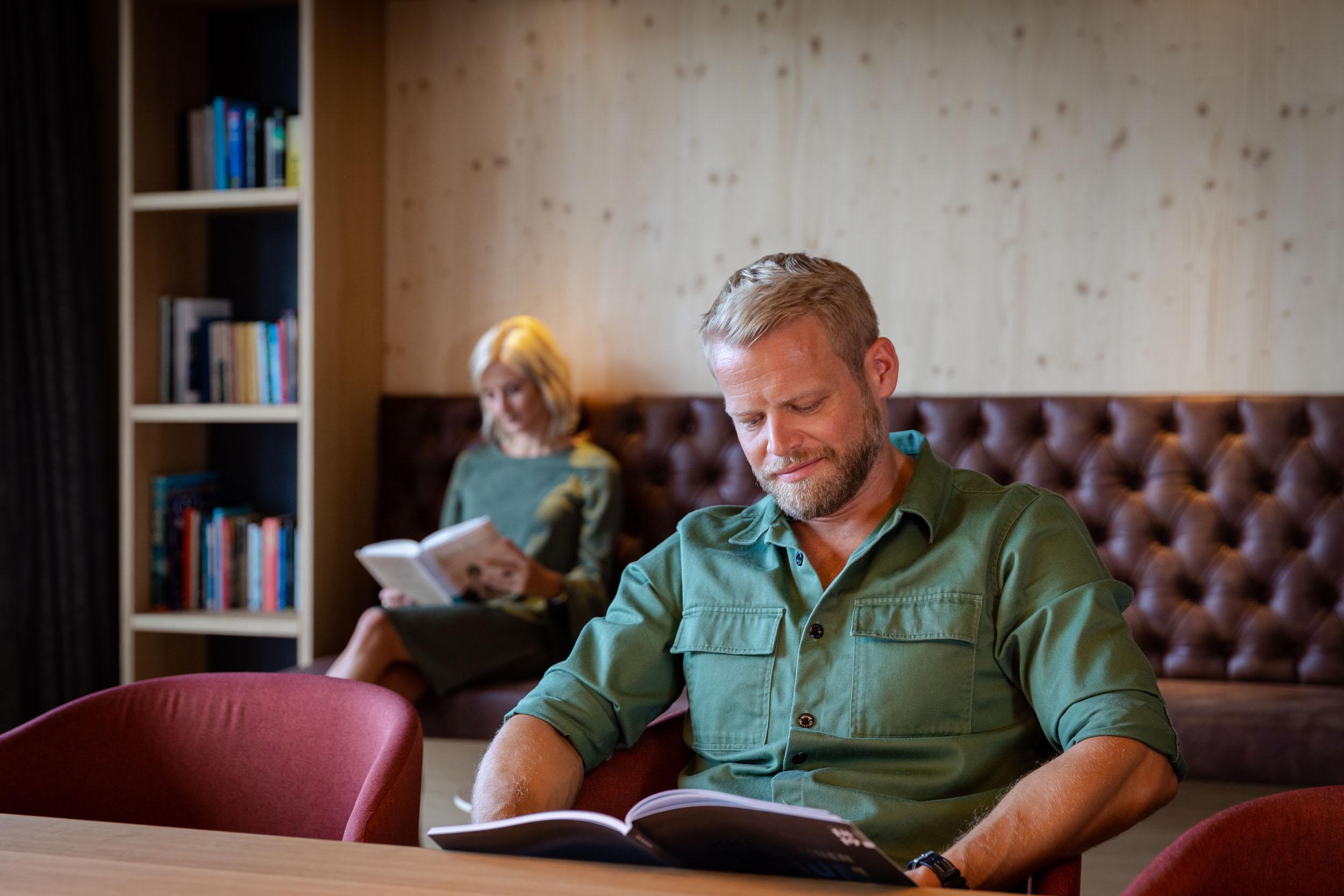 Ein Mann und eine Frau lesen im Business-Hotel eduCARE bei Villach