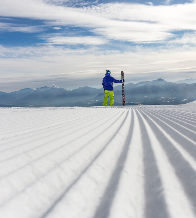 Ein Mann steht im Winterurlaub mit Hund in Kärnten mit seinen Skiern auf der Piste