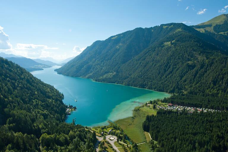 Ein See eingebettet zwischen den Bergen beim Urlaub in Kärnten am See