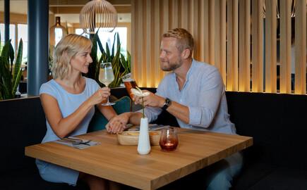 Ein Paar stoßt im Wirtshaus des Hotels mit Seminarguide gemeinsam an