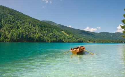 Ein Boot treibt im Familienurlaub am Ossiacher See auf dem Wasser