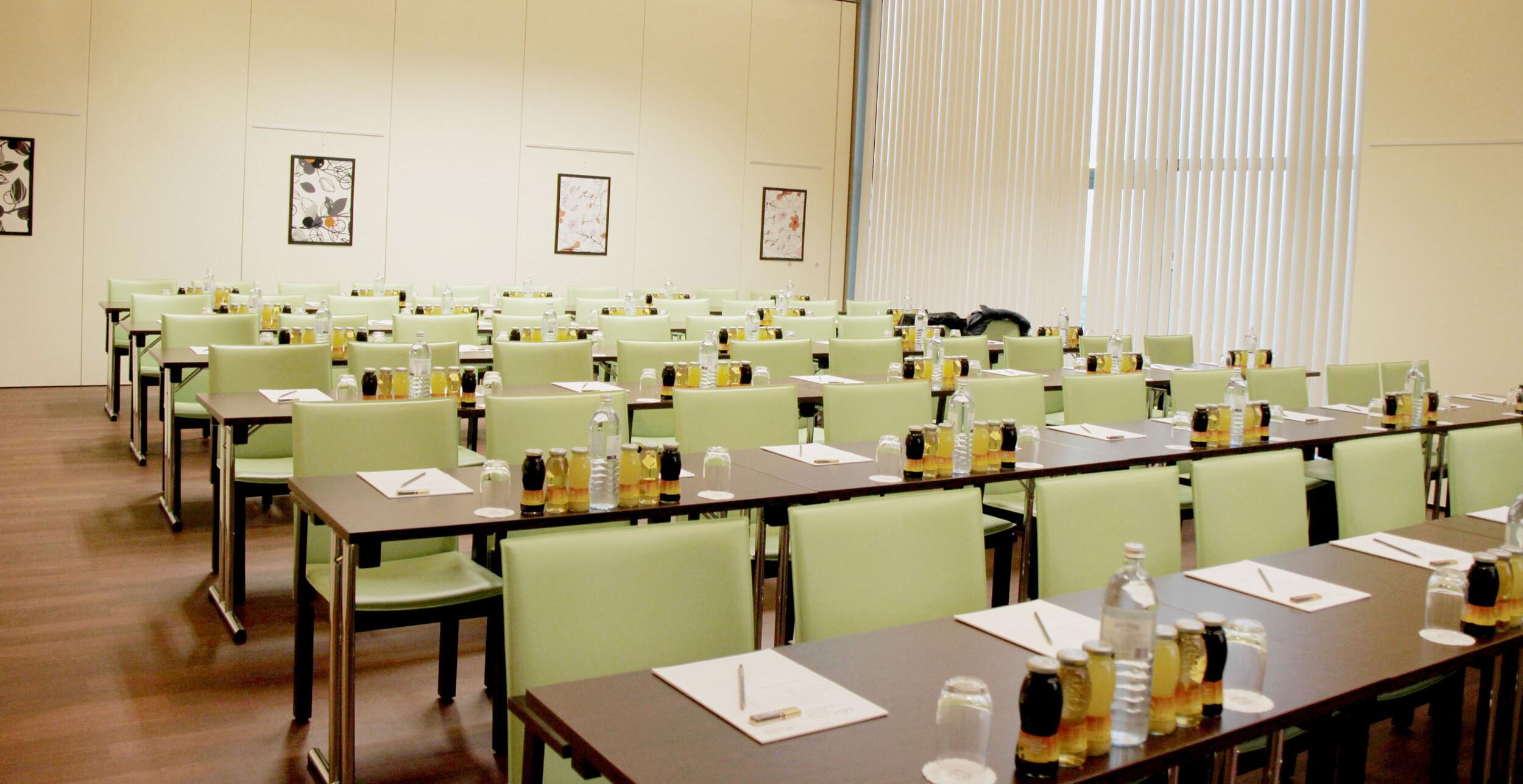 Ein Seminarraum mit vorbereiteten Tischen für Incentives und Firmenevents in Kärnten