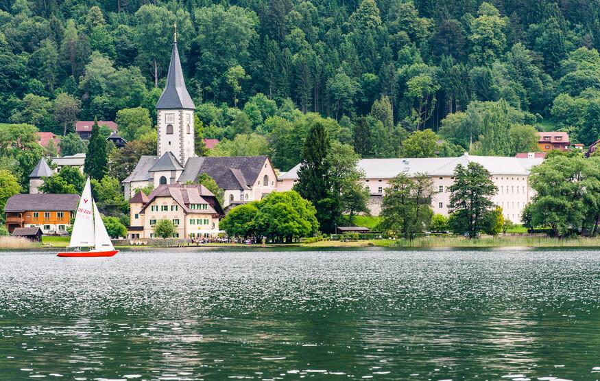 Ein Mann fährt beim Urlaub in Kärnten am See mit dem Boot