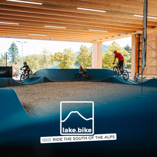 Familienvater fährt mit Kindern im Pumptrack in der lake.bike Region in Kärnten