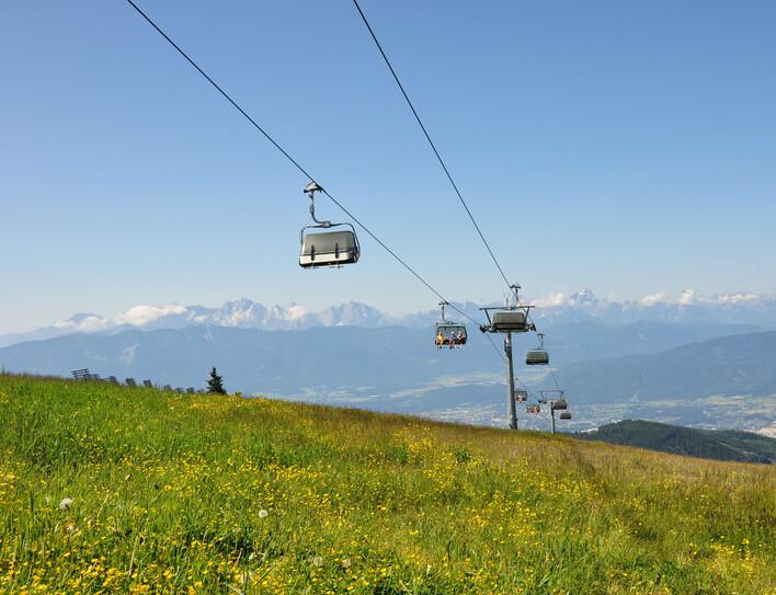 Ein Sessellift fährt den Berg hinauf zu einem Ausflugsziel beim Urlaub im Hotel mit Kärnten-Card