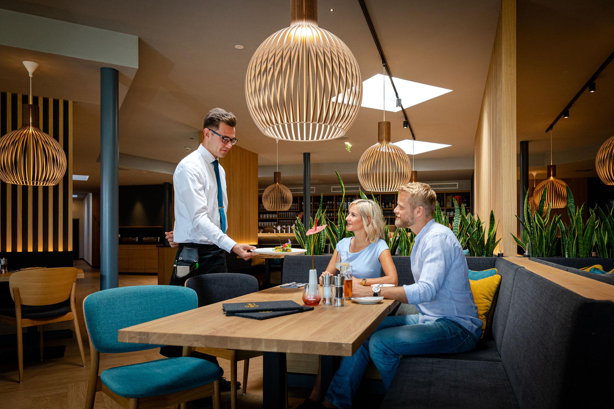 Der Kellner serviert einem Paar im familiären Hotel eduCARE in Kärnten ihr Essen