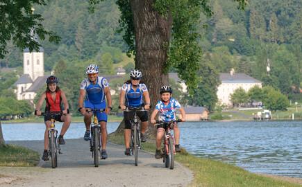 Eine Familie beim Radfahren im Familienurlaub am Ossiacher See