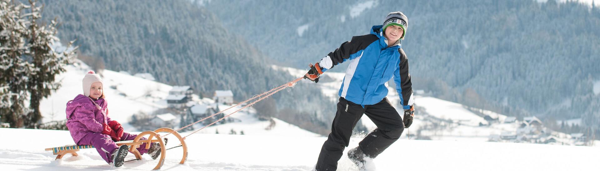 Zwei Kinder beim Schlittenfahren im Skiurlaub an der Gerlitzen Alpe