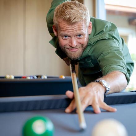 Ein Mann spielt Billiard im Hotel eduCARE am Ossiacher See