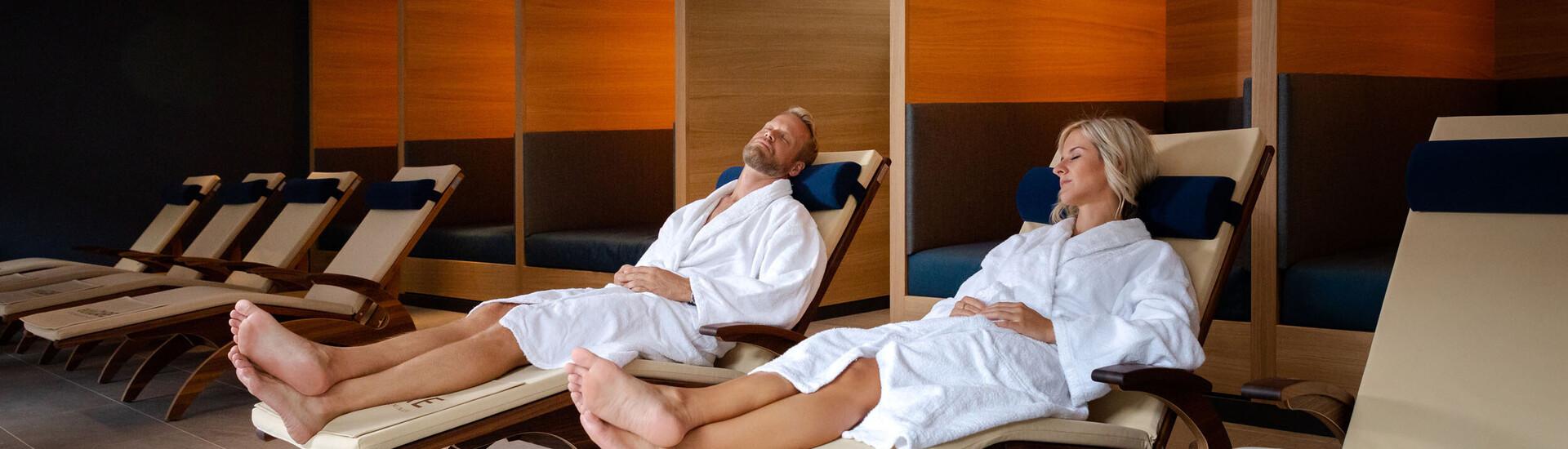 Ein Paar entspannt gemeinsam auf den Liegen im Hotel mit Wellnessbereich am Ossiacher See
