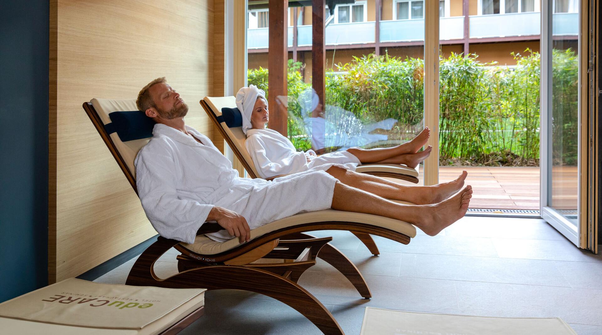 Ein Paar entspannt auf den Liegen im Wellnessbereich vom 4-Sterne Hotel eduCARE in Treffen am Ossiacher See