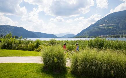 Ein Paar fährt im Urlaub am Ossiacher See mit dem Rad am Ufer entlang
