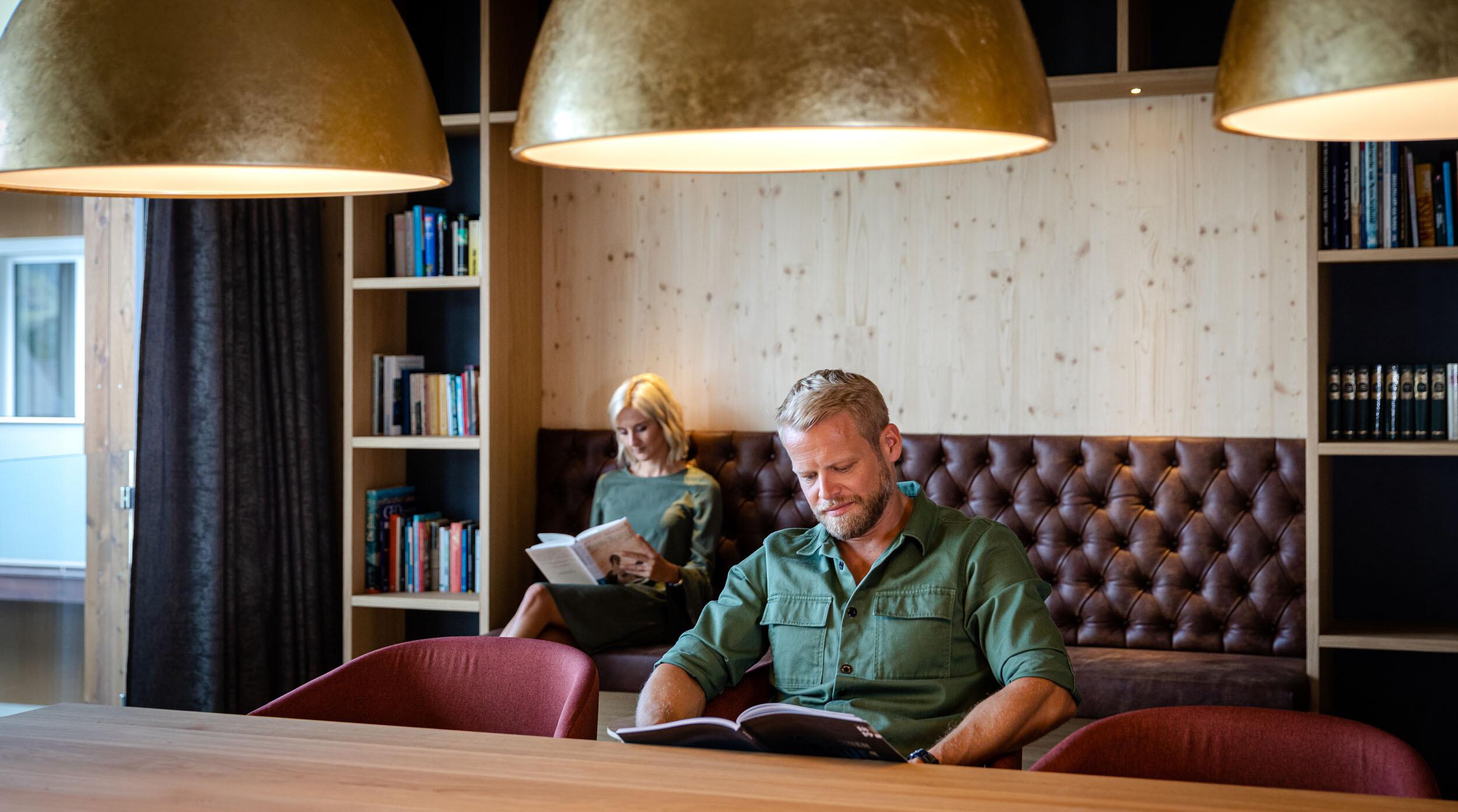 Ein Paar liest im Freizeitraum vom 4-Sterne Hotel eduCARE in Treffen am Ossiacher See