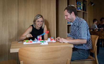 Die Gastgeber vom Hotel mit Seminarguide in Kärnten sitzen im Freizeitraum und spielen ein Spiel