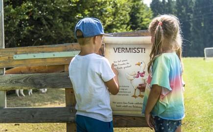 Zwei Kinder stehen vor einem Tiergehege