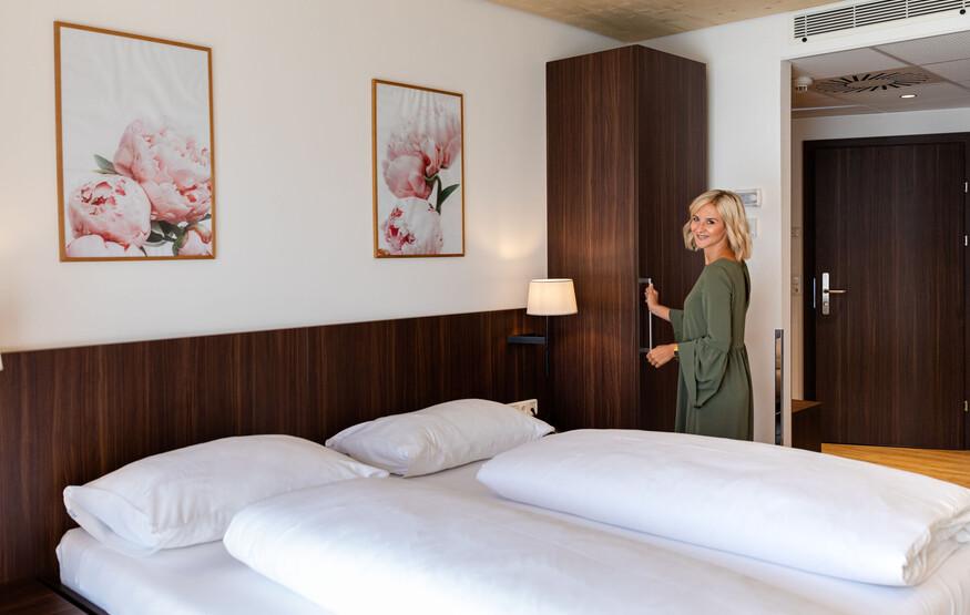 Eine Frau steht im modernen Zimmer im Hotel eduCARE am Ossiacher See