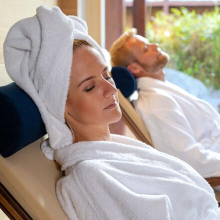 Ein Paar entspannt auf den Liegen im Hotel eduCARE mit Wellnessbereich am Ossiacher See