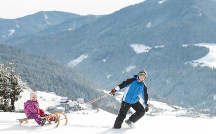 Ein Bub zieht im Urlaub am Ossiacher See ein Mädchen auf der Rodel durch den Schnee