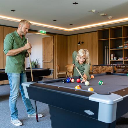 Ein Paar spielt gemeinsam Billiard im Seminarhotel bei Villach am Ossiacher See