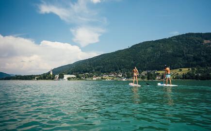 Ein Paar versucht sich beim Urlaub im nachhaltigen Hotel in Kärnten am SUP