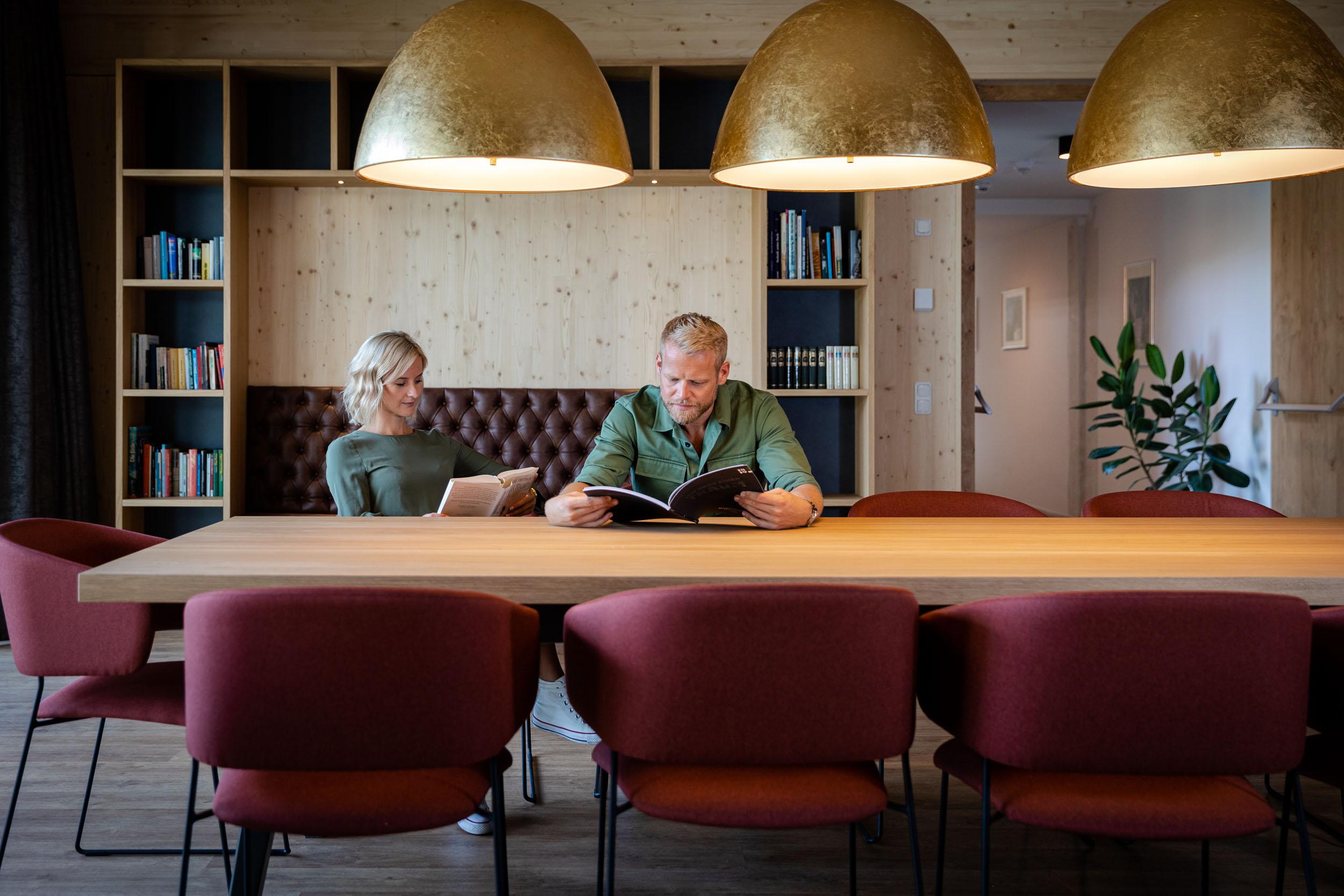 Ein Paar liest entspannt im Urlaub mit den Hotelgutscheinen Österreich