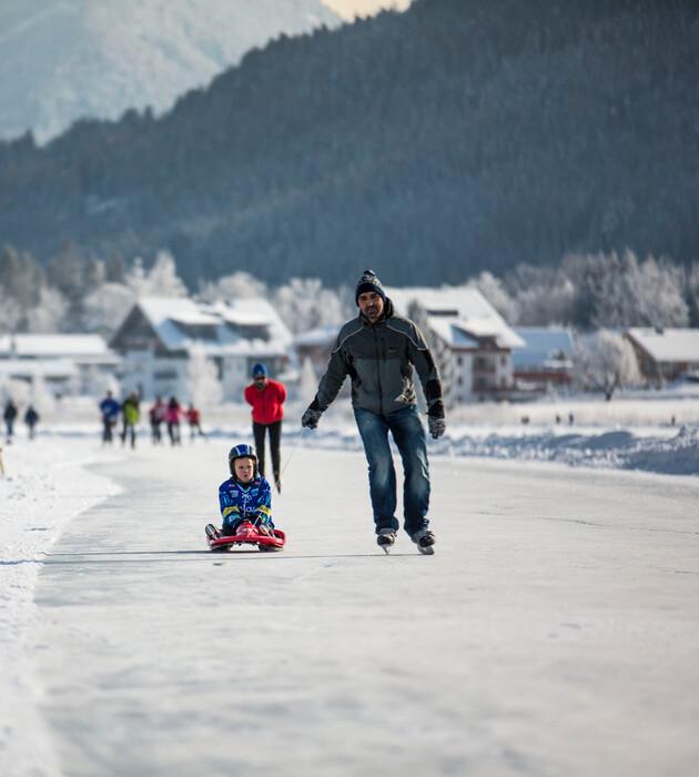 Ein Vater und sein Kind beim Rodeln im Winterurlaub mit Hund in Kärnten