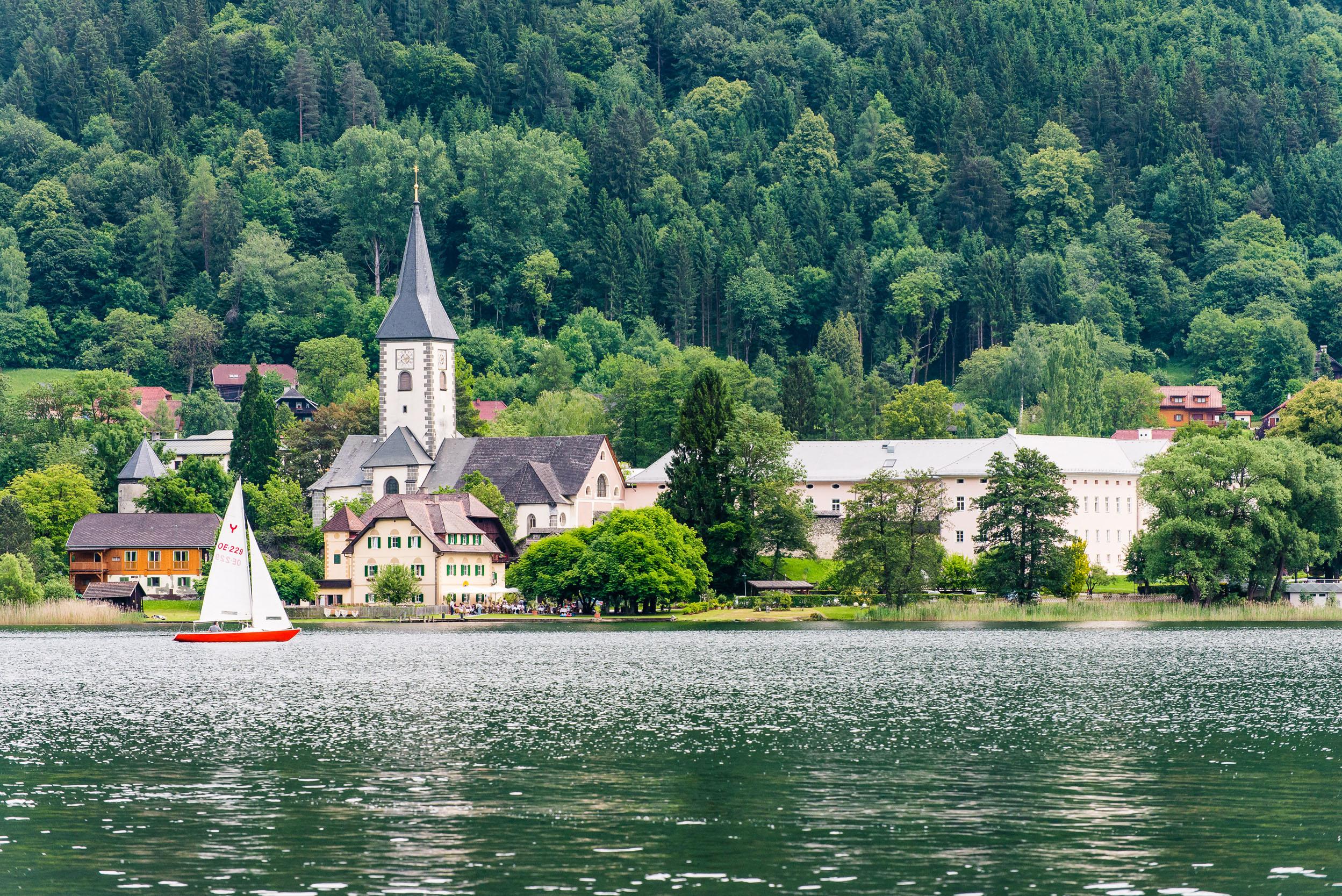 Ein Boot fährt über den See an der Stadt mit vielen barrierefreien Ausflugszielen in Kärnten vorbei