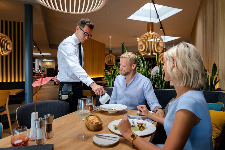 Ein Kellner serviert im 4-Sterne Hotel am Ossiacher See einem Paar ihr Abendessen