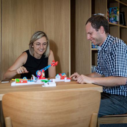 Die Gastgeber vom Seminarhotel bei Villach am Ossiacher See sitzen im Freizeitraum und spielen ein Spiel