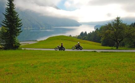 Zwei Motorradfahrer fahren nahe dem Hotel eduCARE bei Villach eine kleine Straße Richtung See entlang