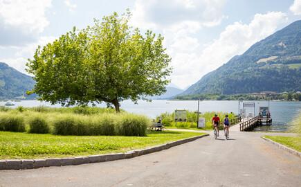 Zwei Radfahrer fahren nahe des Hotels eduCARE bei Villach am See entlang