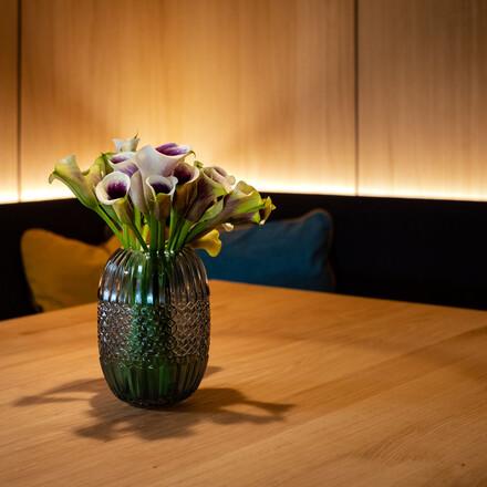 Ein mit Blumen dekorierter Tisch im Wirtshaus vom Hotel eduCARE in Treffen am Ossiacher See