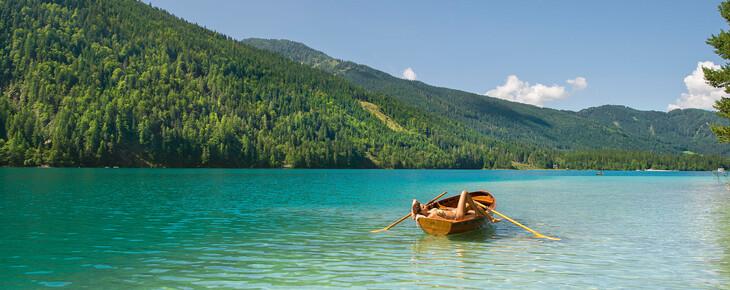 Eine Frau genießt beim Urlaub in Kärnten am See  auf einem Boot die Sonne