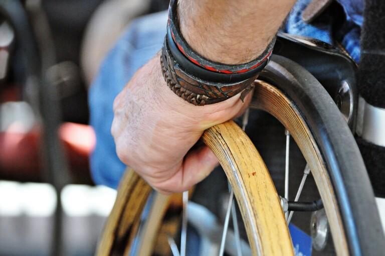 Detailaufnahme von einem Rollstuhlfahrer im Urlaub mit vielen barrierefreien Ausflugszielen in Kärnten