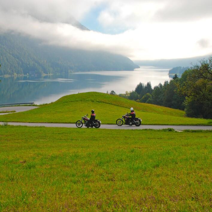 Zwei Motorradfahrer genießen bei einer Veranstaltung in Villach und Umgebung den Ausblick auf den See