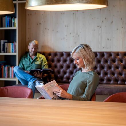 Ein Paar liest im Freizeitraum des 4-Stern Hotels eduCARE am Ossiacher See