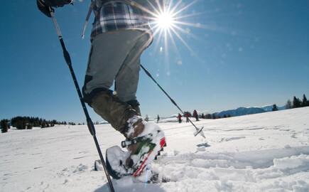 Ein Mann beim Schneeschuhwandern im Urlaub am Ossiacher See