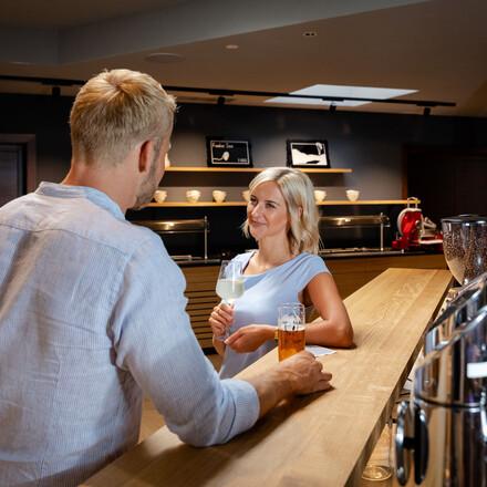 Ein Paar genießt einen Drink an der Bar vom Hotel eduCARE in Treffen am Ossiacher See