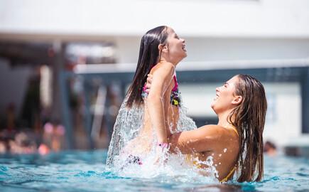 Eine Mutter und Ihre Tochter plantschen beim Urlaub im Hotel eduCARE bei Villach im Pool der Therme