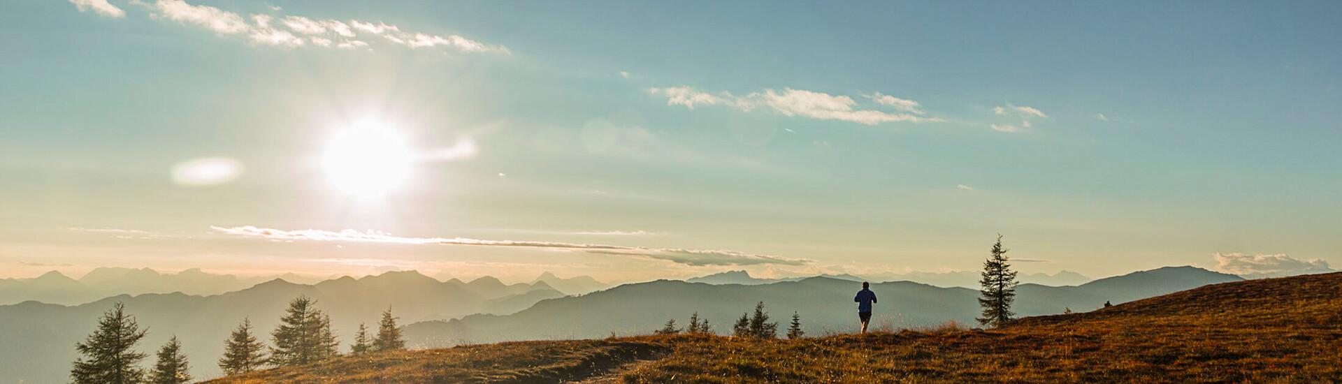 Ein Mann läuft nahe dem Hotel mit Kärnten-Card durch die Landschaft