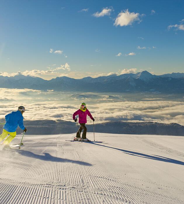 Ein Paar beim Skifahren im Urlaub an der Gerlitzen