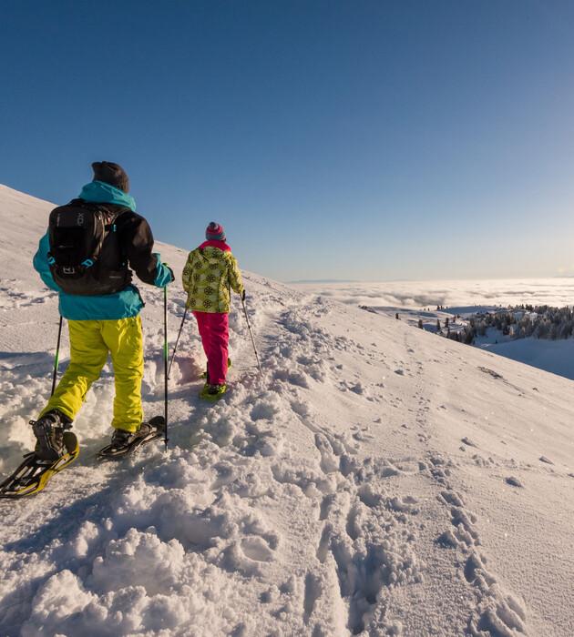 Ein Paar beim Schneeschuhwandern im Winterurlaub mit Hund in Kärnten