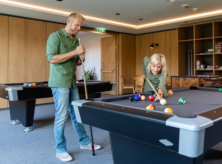 Ein Paar spielt gemeinsam Billiard im 4-Stern Hotel eduCARE am Ossiacher See