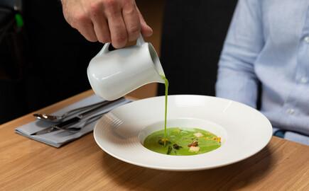 Ein Kellner serviert einem Gast das Essen im Hotel mit Seminarguide in Kärnten