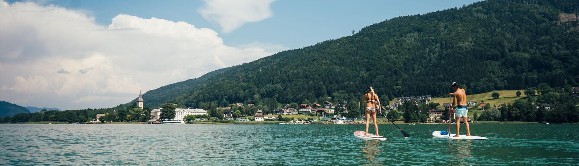 Ein Paar beim Stand-up-Paddling im Urlaub mit den Hotelgutscheinen vom eduCARE in Österreich