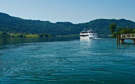 Ein Schiff fährt nahe dem Hotel mit Kärnten-Card über den See