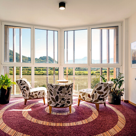 Eine gemütliche Sitzecke mit Panoramablick im Zimmer des Hotels eduCARE am Ossiacher See