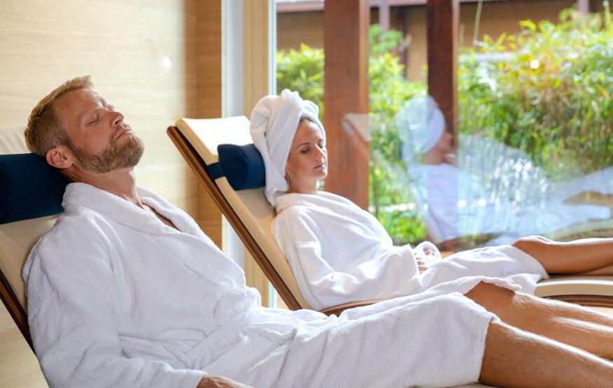 Ein Mann und eine Frau entspannen im Wellnessbereich des Hotels eduCARE in Treffen am Ossiacher See