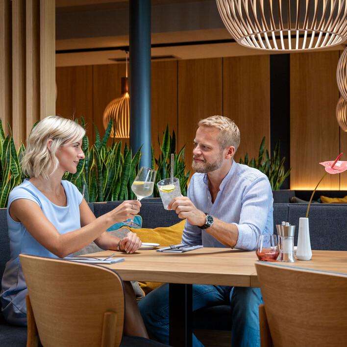 Ein Paar stoßt im Restaurant des 4-Sterne Hotels eduCARE in Treffen am Ossiacher See gemeinsam an