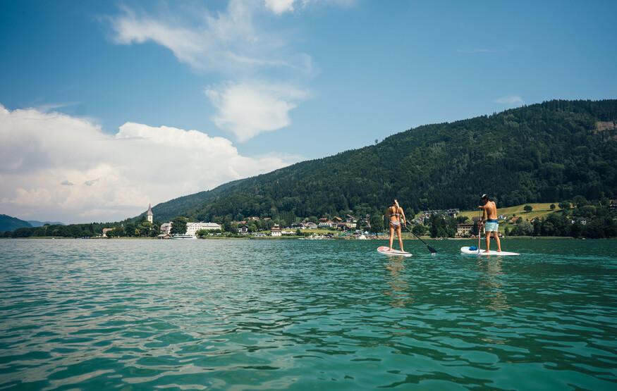 Ein Mann und eine Frau beim Stand-up-Paddling im Urlaub in Kärnten am See